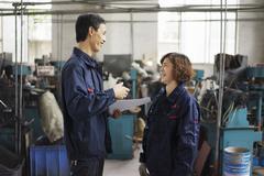 Supervisor explaining to worker in crane factory, Jiangsu Province, China Stock Photos