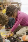 Toddlers playing jigsaw puzzle in classroom Stock Photos
