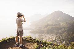 Young man photographing at Lake Atitlan on digital camera, Guatemala - stock photo
