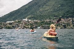 Young adult friends kayaking on  Lake Atitlan, Guatemala - stock photo