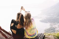Rear view of two female friends taking smartphone selfie at Lake Atitlan, - stock photo
