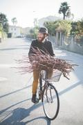 Young man carrying bunch of sticks on bike Stock Photos