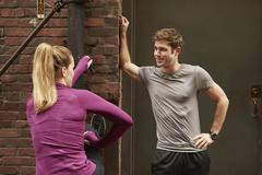 Young male and female runners warming up in alleyway - stock photo