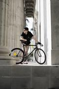 Bike messenger taking break beside column - stock photo