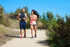 Mid adult man and woman jogging together along rural pathway - stock photo