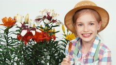 Portrait cute flower-girl child in hat sitting near flowers and eating lollipop - stock footage