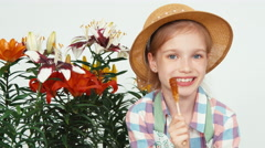 Portrait cute flower-girl child sitting near flowers and eating lollipop Stock Footage