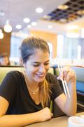 Young woman eating with chopsticks in restaurant, Manila, Philippines Kuvituskuvat