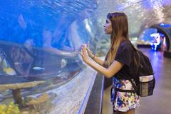 Young woman watching fish in seawater aquarium, Manila, Philippines - stock photo