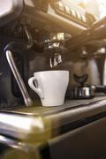 Coffee cup under coffee machine in cafe Stock Photos