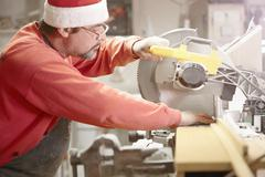 Cabinet maker using circular saw in workshop - stock photo