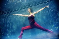Mature woman wearing red yoga pants and vest, in yoga position, underwater view Stock Photos