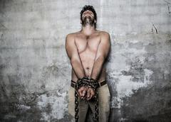 Bare chested young man with chains wrapped around his wrists - stock photo