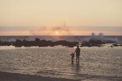 Silhouetted mother and female toddler paddling in sea looking out at waves - stock photo