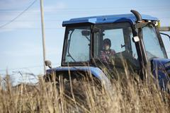 Boy farmer driving tractor in dairy farm field - stock photo