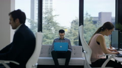 4K Business team working in modern office, focus on man using laptop by window Stock Footage
