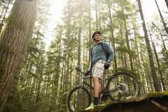 Young man standing with mountain bike in forest, low angle view Stock Photos