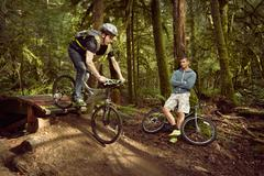 Young man riding mountain bike over ramp, in forest, while friend watches Stock Photos