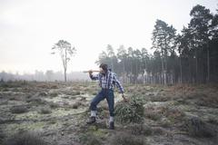 Mature woodsman standing in forest clearing with axe over his shoulder Stock Photos