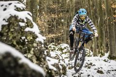 Young male mountain biker speeding on snow covered rocks in forest - stock photo