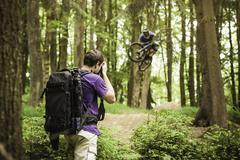 Young male photographer photographing mountain biker in forest - stock photo