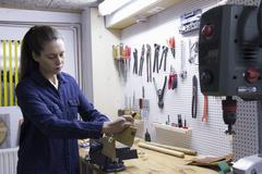 Young female carpenter planing timber in workshop vice - stock photo