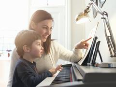 Mother pointing at sheet music to teach son to play piano at home - stock photo