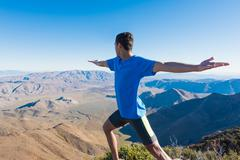 Male trail runner warming up whilst looking out at landscape on Pacific Crest - stock photo