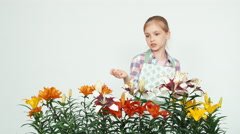 Close up portrait flower-girl advertises flowers and smiling at camera on white Stock Footage