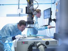 Electronics workers checking components in clean room laboratory - stock photo