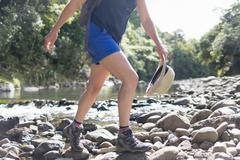 Hiker walking among stones in shallow stream, Waima Forest, North Island, NZ - stock photo