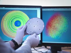 Scientist checking test map of silicon wafer in laboratory, close up - stock photo