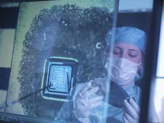 Electronics worker holding silicon wafer reflected in screen in clean room Kuvituskuvat