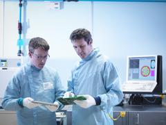 Workers checking electronics in clean room laboratory - stock photo