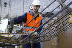 Factory worker attaching steel mesh at concrete reinforcement factory - stock photo