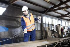Factory worker moving steel rod at concrete reinforcement factory - stock photo
