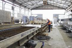 Factory worker on production line in concrete reinforcement factory - stock photo