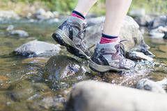 Hiker's feet walking on stones in shallow stream - stock photo