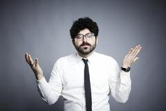 Portrait of young man, hands open in questioning expression - stock photo
