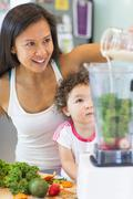Mid adult woman making smoothie for toddler niece in kitchen - stock photo