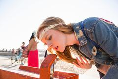 Young woman at drinking fountain, Santa Monica Pier, Santa Monica Beach, US Kuvituskuvat