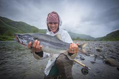 Fisherwoman holding up caught pink salmon in river, Kodiak, Alaska, USA - stock photo