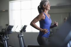 Mature woman running on gym treadmill Stock Photos