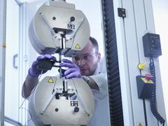 Scientist tests tensile strength of carbon fibre in carbon fibre laboratory - stock photo