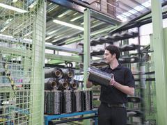 Worker carrying carbon fibre thread in carbon fibre factory Stock Photos