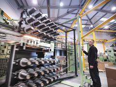 Worker operating carbon fibre loom in carbon fibre factory Stock Photos