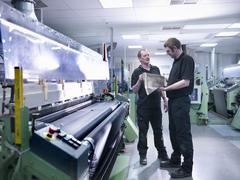 Workers inspecting carbon fibre sample in carbon fibre factory - stock photo