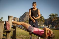 Young woman doing sit ups on wooden workbench in  park - stock photo