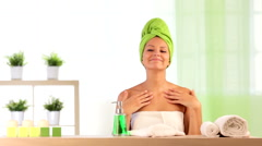 Woman wearing towels applies beauty treatment at health spa indoor Stock Footage