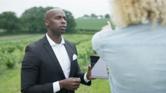 4K Businessman outdoors with farmer negotiating & shaking hands on a deal.  Stock Footage